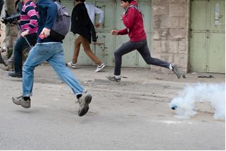 Manifestantes fogem de gás lacrimogênio durante um protesto contra a ocupação israelense na cidade de Hebron, Cisjordânia[1]