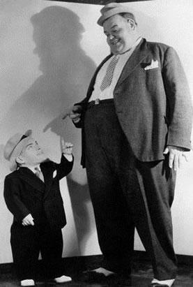 A figura mostra um indivíduo com estatura normal (à direita) ao lado de uma pessoa com nanismo (à esquerda)