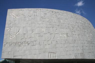 Acima, o prédio moderno que ocupa o lugar da antiga biblioteca de Alexandria, no Egito
