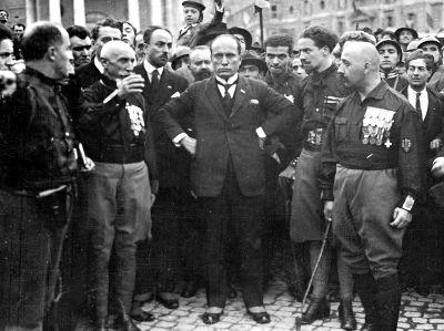 Acima, Mussolini, no centro da imagem, rodeado por companheiros fascistas