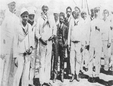 João Cândido, o homem alto e sorridente ao centro, principal líder da Revolta da Chibata. Foto de O Malho, de 03/12/1910